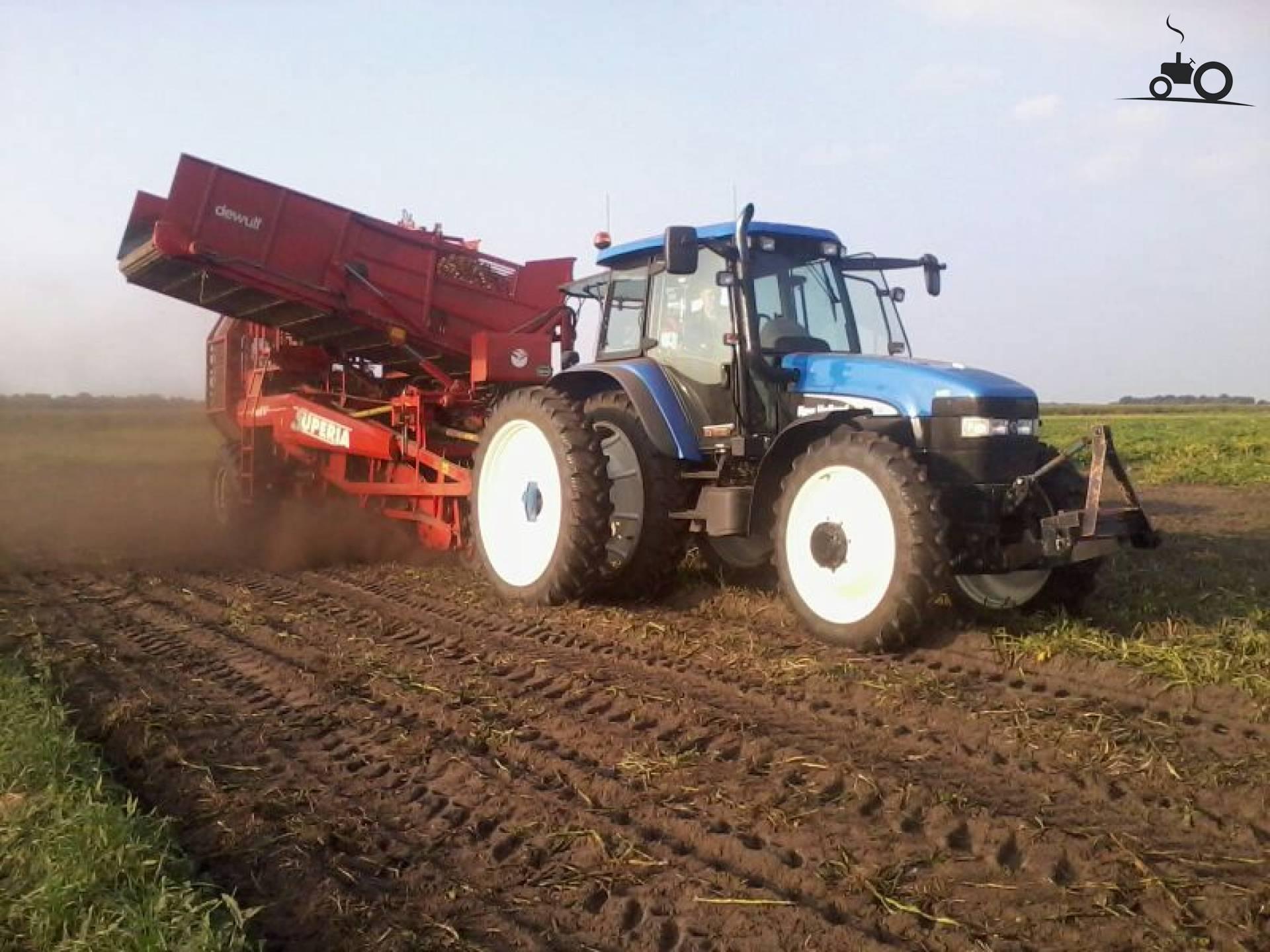 Foto van een New Holland TM 130, druk bezig met Aardappels rooien.