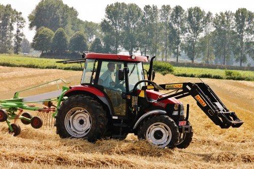 Foto van een Case IH JX 70, bezig met gras harken. Het heeft ook hier een goede bui regen gekregen, nu schijnt het zonnetje dus dat word stro keren geblazen. Foto is gemaakt in Sint-Margriete(BE).