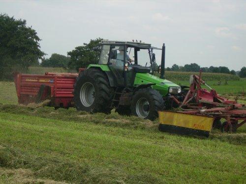 Foto van een Deutz-Fahr AgroXtra 6.07, bezig met gras harken en gedorst hooi toevoegen in 1 werkgang. Hier word bij de kuil nog wat ingekuilde mais bijgedaan,word een mengkuil voor droge koeien!