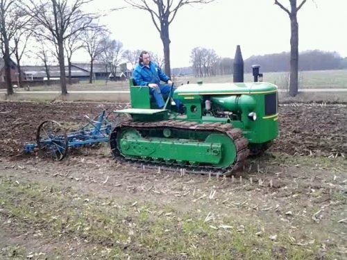 Foto van een Deutz Rups trekker, bezig met ploegen / eggen. cultiveren met rupstrekker 45cm diep erdoor alsof het niets is. trekker van 60pk van deutzmagirus. opbeuren gaat wielaangedreven. als je aan touw trekt grijpt een tandheugel in een tandwiel en beurt daardoor de cultivator uit de grond