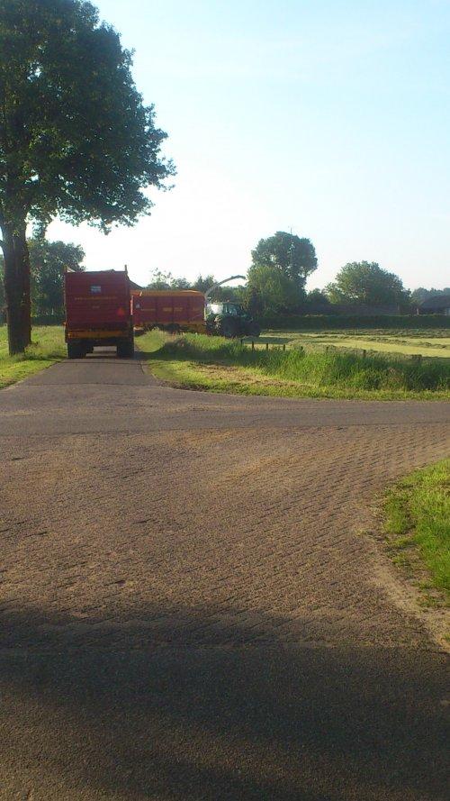 Foto van een Deutz Meerdere, bezig met gras hakselen. Loonbedrijf peters haps in vroege ochtend aan gras hakselen.