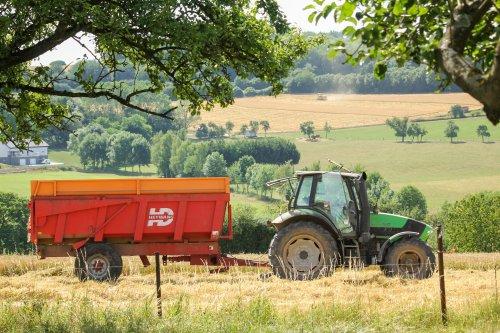Een airco-loze Deutz-Fahr wacht op de combine.. Geplaatst door Fendt940 op 10-07-2017 om 21:18:37, op TractorFan.nl - de nummer 1 tractor foto website.