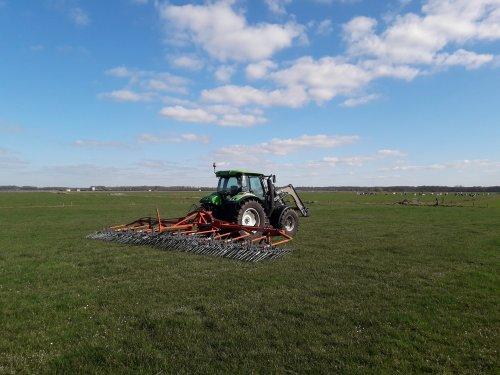 Foto van een Deutz-Fahr Agrotron K 90  Paar percelen wiedeggen. Ondertussen de koeien op de achtergrond 3 dagen buiten.  Het mestrijden gebeurt nu nadat de koeien erover zijn geweest.