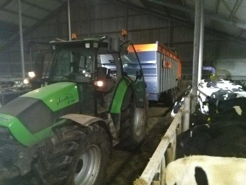 Foto van een Deutz-Fahr Agrotron K 100, voerwagen dagelijks aan en afkoppelen om het voer aan te schuiven.