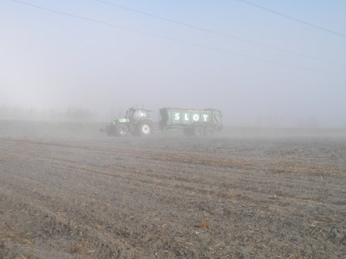 Foto van een Deutz-Fahr Agrotron TTV 1160, bezig met bemesten. bezig in de mist met de strooier in vijfhuizen