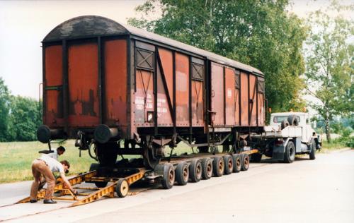 Foto van een Faun straßenzugmaschine, met een Culemeyer 16 wielige straßenroller, bezig met het lossen van een wagon in 1985.