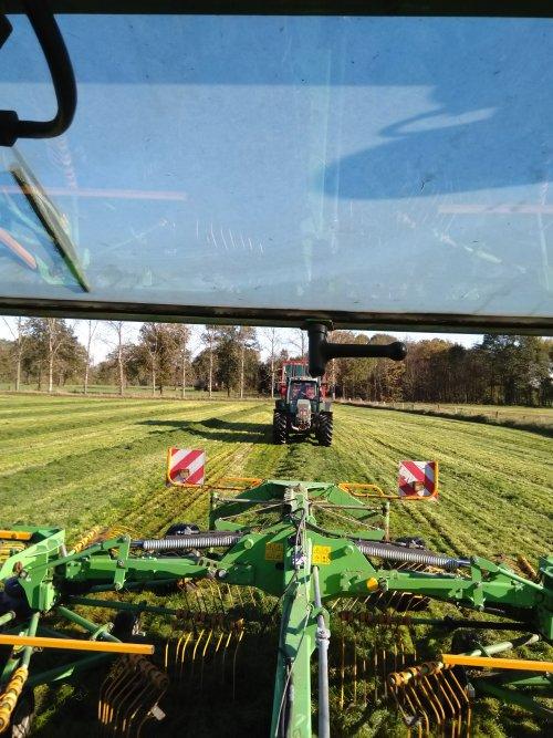Foto van een Fendt 716 bezig met gras oprapen en ervoor een 311 lxa die het laatste gras bij elkaar harkt.