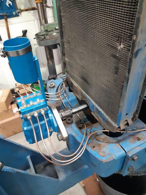 Foto van een Fordson Doe Triple D leidingwerk voor het doorgeven van de bediening van de achterste naar de voorste trekker. Gezellig druk onder in de voorneus.