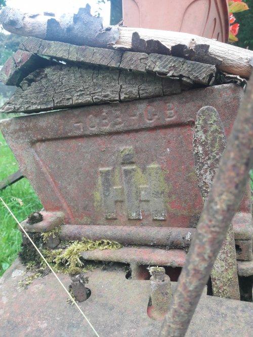 Foto van een International Logo op een oude zaaimachine die nu dienst doet als bloembak ergens onderweg in vielsalm.