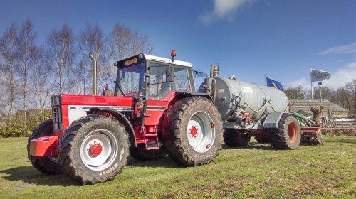Foto van een International 1055, druk bezig met Bemesten, op het werk de Inter eens voor de tank geknoopt.