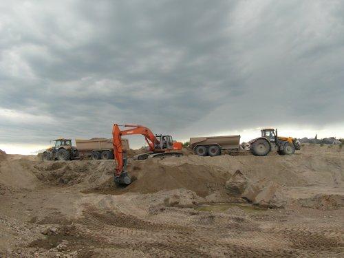 Foto van een JCB Meerdere, bezig met dumperen. JCB 8250, Hitachi 230, JCB 7270. Stage Alberta, Canada '12.
