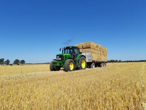Foto van een John Deere 6930 Premium bezig met stro rijden. Geplaatst door cb6520 op 30-06-2019 om 14:38:11, op TractorFan.nl - de nummer 1 tractor foto website.