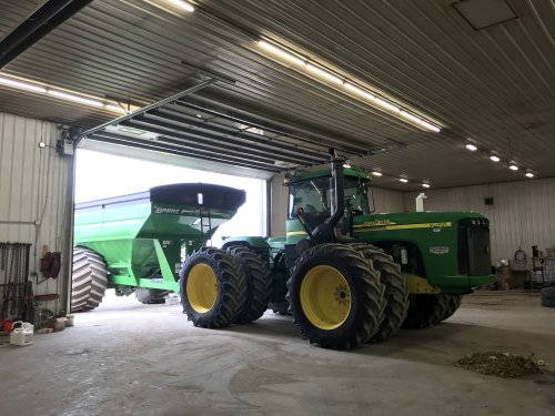 Foto van een John Deere 9420 klaar maken voor de graanoogst. Nieuwe overlaadwagen er achter, en even poetsen natuurkijk