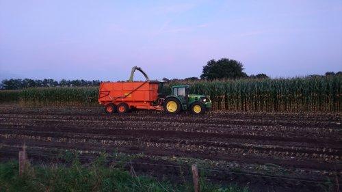 Loonbedrijf Jan Rauw uit Achterberg aan het maishakselen in de avondzon, met Claas Jaguar 890 en John Deere 6330.