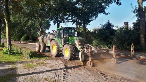 Foto van een John Deere 6130R, de combinatie om de weg schoon te houden, inmiddels een slang onder de trekker door liggen, zo kan er doormiddel van de ketsplaat voorop de bezem water voor het vegen worden toegediend, werkt perfect zo👌