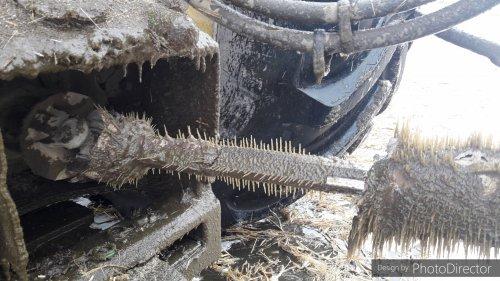 Foto van een John Deere 8295R, waarvan de aftak as vol met kleine stront ijspegels hangt.  De combinatie van -20ºC en een langzaam lekkend klepje voor op de tank zorgt voor mooie ijssculpturen.   Nadeel is wel, als je ergens bij moet voor controle of de strontkar moet smeren ben je standaard een hamer nodig, wat soms moeilijk uit te leggen is als je iemand vraagt om een hamer als je wilt smeren.   Zie andere foto voor meer uitleg: https://www.tractorfan.nl/picture/1336119/user/32782/