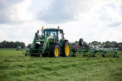Foto van een John Deere 6110 de oude 6110 met krone 11,2 meter brede schudder het gras los aan het gooien