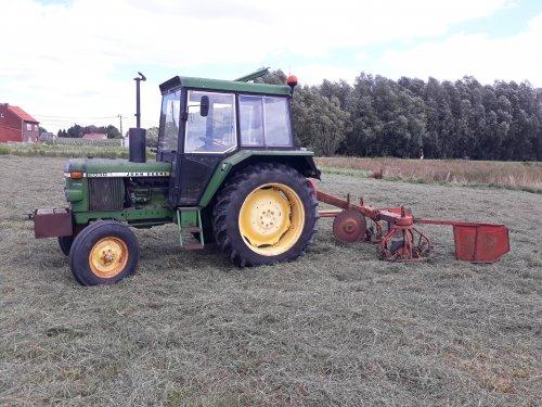Foto van een John Deere 2030 met een Kemper Heuromat druk bezig met het nieuwe ingezaaide gras te schudden