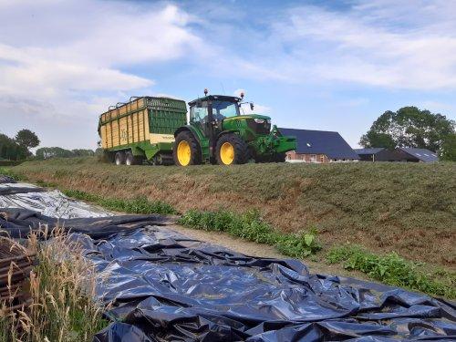 John Deere 6140R, met Krone XXL doseerwagen bezig met inkuilen, bij de overburen.. Geplaatst door Henk 1120 op 06-09-2020 om 12:46:18, op TractorFan.nl - de nummer 1 tractor foto website.