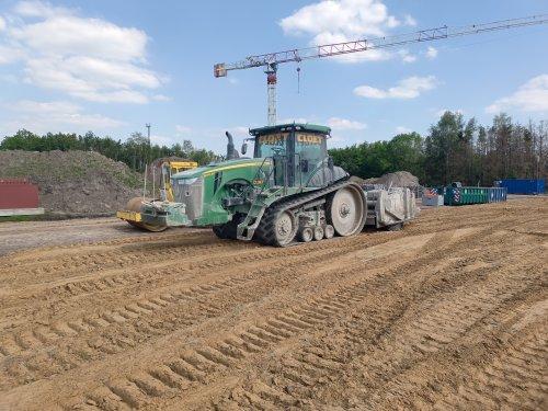 Foto van een John Deere 8370RT, de firma Cloet is hier bezig met een kalk-cementmengsel in te frezen om de grond te stabiliseren.