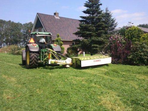 Foto van een John Deere 6320 SE, bezig met gras maaien. Pa bezig met de kanten van de wei. (stukje voor de stal.