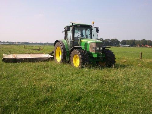 Foto van een John Deere 6320 SE, bezig met gras maaien. een wei waar de koeien in hebben gelopen glad maaien!