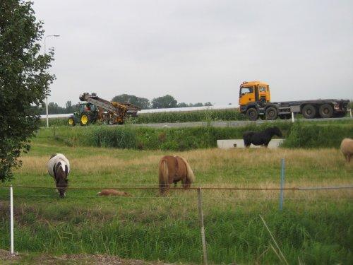 Foto van een John Deere 6320 SE met champost transportband van v Herwijnen met de vrachtwagen er achteraan