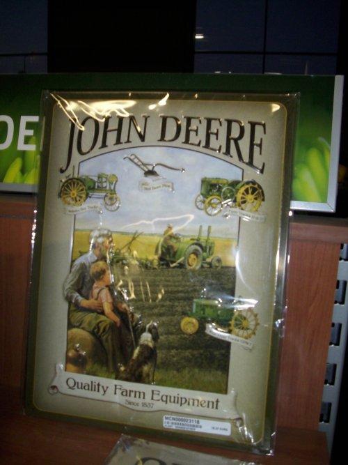 Foto van een John Deere souvenirs, bezig met poseren.  John Deere wandplaat met o.a. de John Deere ploeg waar het allemaal me begon en de Waterloo Boy.  1837 - 2012: 175 years Quality Farm Equipment!