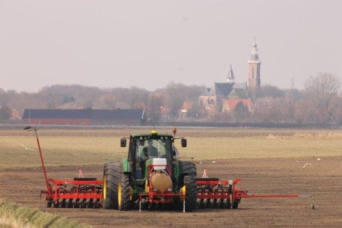 Foto van een John Deere 6320, bezig met zaaien. Loonbedrijf Paridaen, uien aan het zaaien voor een boer in sint kruis. Met de kerk van Aardenburg op de achtergrond, toppertje?