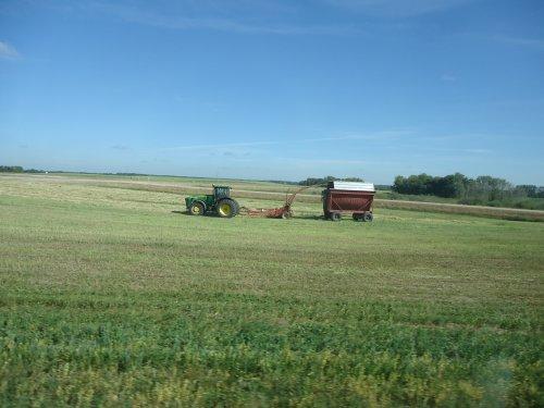 Foto van een John Deere Onbekend, bezig met gras hakselen.ik weet het type niet,john deere is niet mijn merk.vond dit wel een heel mooi systeem met die kar er bij aan.