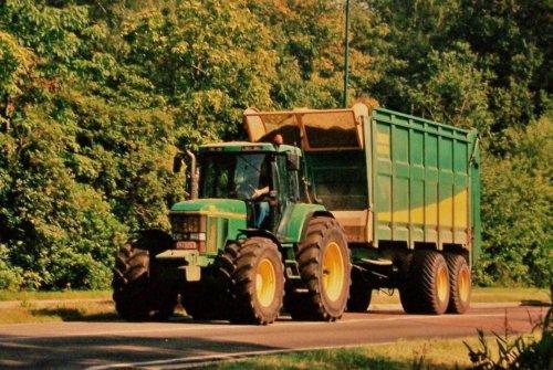 Foto van een John Deere 7010 Serie, bezig met maïs inkuilen. Fraaie combi van het bijzonder sympathieke loonbedrijf Paulussen, onderweg in okt. 2003