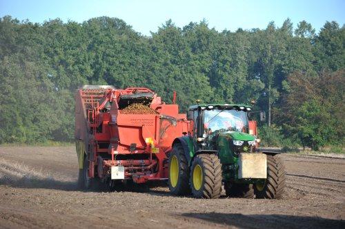 Foto van een John Deere 6150R, bezig met aardappels rooien.. Geplaatst door westerveldwestendorp op 07-02-2014 om 17:45:04, op TractorFan.nl - de nummer 1 tractor foto website.