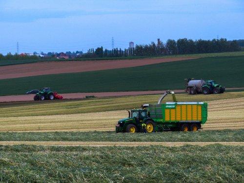 Foto van een John Deere 7720, bezig met snijrogge hakselen. De allereerste hectare's voor de biogas in tongeren . En meteen het land klaarleggen om er mais op te zaaien.