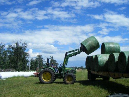 Foto van een John Deere 6430. In Canada bezig met pas geperste balen in de wikkelaar aan het zetten.