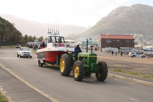 Foto van een John Deere 3140 die wordt gebruikt om boten uit het water te slepen in Hout Bay, Kaapstad, Zuid-Afrika