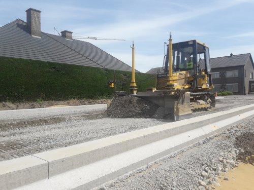 Foto van een Komatsu Bulldozer vandaag bezig met de bedding te nivelleren om maandag asfalt te leggen.