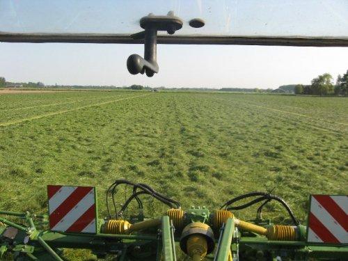 Foto van een Krone KW15.02/14T, bezig met gras schudden.  even een x doorsteken kijken hoe breed die is.