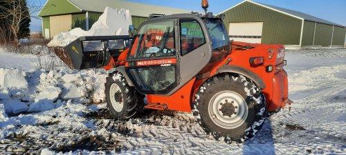 9 februari 2021 foto van een Manitou MLT 634 120 LSU.  Hier zijn we bezig om de sneeuw uit de sloot te scheppen. Dit huis is niet aangesloten op de persriolering. De wc wilde gisteren niet meer doorspoelen, dus de overloopbuis die vanuit de sceptictank naar de sloot gaat maar vrij proberen te graven. We hebben de buis niet gevonden, maar de wc loopt weer goed door, dus maar zo gelaten.  De bak aan de verreiker is een wifo-bak. We hebben deze bak om vlak over beton te kunnen scheppen. We scheppen er liatrisbollen mee in de spoellijn. Dan moet je hem niet helemaal vol scheppen, want dan kun je hem niet tillen.  De bak is 2,25 m breed om goed aardappelen mee tussen de bovengrondse kanalen te kunnen scheppen. De verreiker zelf is 2,4 m breed, dus het is wel oppassen dat je dan niet over de aardappelen rijdt.