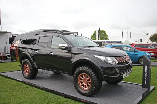 Persfoto van een Mitsubishi L200, opgebouwd as racesimulator.  The Mitsubishi L200 eSports Concept, winner of the inaugural Mitsubishi Motors in the UK Truck King Battle, has today made its public debut at the Mitsubishi Motors Badminton Horse Trials.  On display at the Mitsubishi Motors Brand Experience stand from Friday 3rd until the climax of the horse trials on Sunday 5th May, the L200 eSports Concept is based on the 'Truck King Battle' winning entry from Joanne Tulloch of Livery Dole Mitsubishi in Exeter, whose concept of an eSports gaming truck gained the highest online engagement across the social media channels of Mitsubishi Motors in the UK during the competition. This winning entry has been realised thanks to Mitsubishi Motors in the UK and Ralph Hosier Engineering who had the task of building this unique show vehicle.  Based on a standard Mitsubishi L200, this heavily modified show truck benefits from a chassis extension of 800mm and has been widened by 80mm to enable it to house a twin gaming area. Each of the two race simulator gaming set-ups is complete with a racing seat and Logitech G920 Driving Force Racing wheel, pedal box and gear shifter. Xbox One consoles are linked to curved 24-inch LED screens which are being used to run Forza Horizon 4.  The rear tailgate has been heavily modified and now incorporates a set of fold-down steps to allow easier access to the gaming area, which itself is covered with a bespoke fabrication to allow for the additional headroom required. The rear area is completed with a coffee machine and refreshment bar, allowing for hours of uninterrupted gaming. Two 22-inch LED screens are also situated on the outside of the vehicle to allow onlookers to see what is happening and keep track of the game progress but can be folded away into the rear area during transportation. All of this technology is powered a roof-mounted 150w solar cell, which is capable of charging up the four 105Ah deep-cycle leisure batteries to give up to 