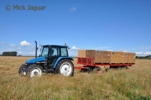 New Holland 5635 met platte wagen en houten kisten, wachtend op een lading graszaad.  Filmpje? -> https://www.tractorfan.nl/movie/46922/