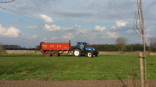 Foto van een New Holland T 6030 Plus bezig met vast mest openrijden met een record S1200. Geplaatst door O N op 31-03-2017 om 20:53:41, op TractorFan.nl - de nummer 1 tractor foto website.