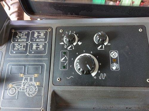 Foto van een New Holland TM 135. De bediengspanneel van de hef.  Weet iemand wat die grotere onderste knop instelt? Zijn helaas 't boek kwijt en op 't grote www is weinig te vinden.