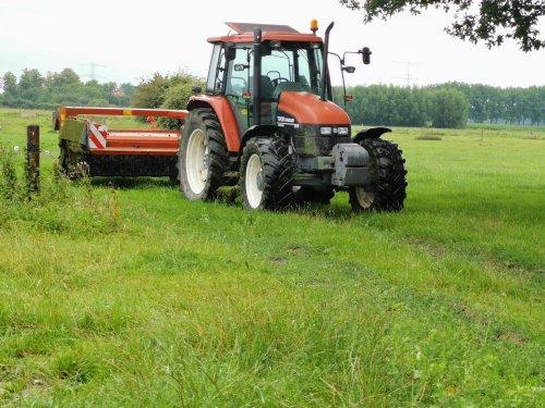 Foto van een New Holland TS 100 druk aan het grasmaaien.. Geplaatst door joostmc-cormick op 12-09-2020 om 10:19:13, met 2 reacties.