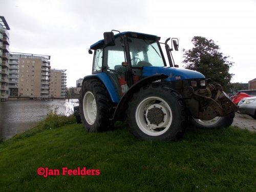 Foto van een New Holland TL 90 , In Schiedam voor transport maaiboot (Okt 2020). Geplaatst door Jan F op 13-10-2020 om 18:45:47, op TractorFan.nl - de nummer 1 tractor foto website.