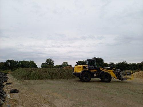 Foto van een New Holland W 170 die klaar is met het vastrijden van de graskuil voor Verschoor fourage.