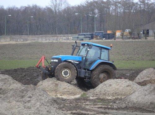 Foto van een New Holland TM 120  Met het uitgraven van de put voor de nieuwe stal is al de zwarte grond over het land verspreidt op hoopjes. Toen er in het voorjaar weer wat moest gaan groeien moest het vlak gemaakt worden, alleen was het te nat om dit met de ahlmann te doen. Dus dan zo maar!  30-3-2013