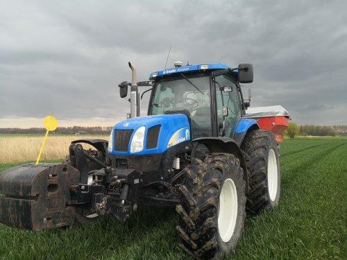 Foto van een New Holland TS 110 A, onder dreigende wolken nog snel de tarwe wat bij strooien!. Geplaatst door NHtvt135 op 06-05-2021 om 14:59:38, met 2 reacties.