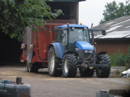 Foto van een New Holland TS 115, bezig met poseren. voor de Peecon 24 kuubs mengwagen. Geplaatst door sebas-casepower op 16-08-2010 om 20:00:14, op TractorFan.nl - de nummer 1 tractor foto website.