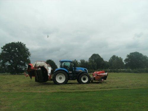 Foto van een New Holland T 7060, bezig met gras maaien. combinatie van loonbedrijf/melkveebedrijf vossebelt uit rijssen