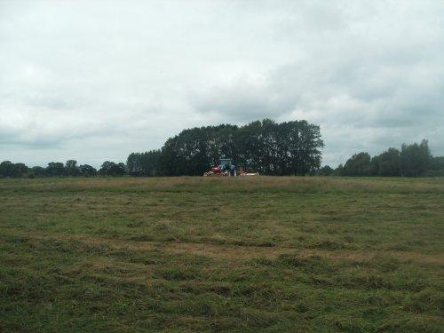 Foto van een New Holland T 7060, bezig met gras maaien. combinatie van loonbedrijf/melkveebedrijf vossebelt